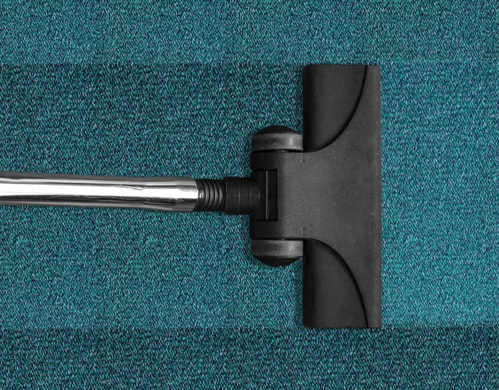 Image of carpet being cleaned with carpet shampooer.